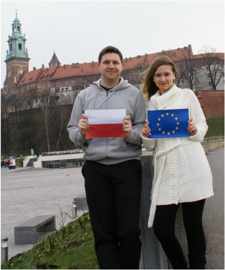 A young Polish couple in front of Wawel Castle, Krakow holding up the Polish and European Union Flags