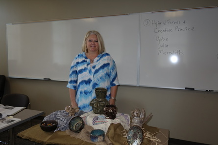 New College Life Track student Karen Burns displaying her pottery together with the work by folk potter Jerry Brown that inspired her.