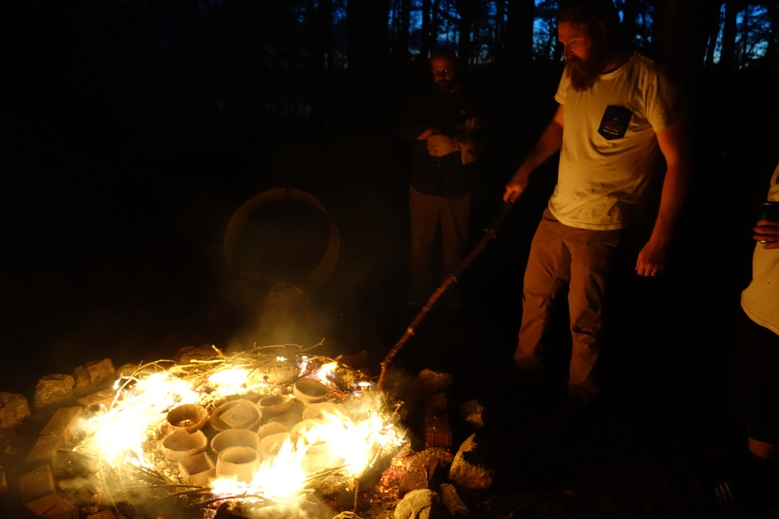 New College student Andrew Seymour tending the fire during an outdoor pottery firing at Moundville State Park
